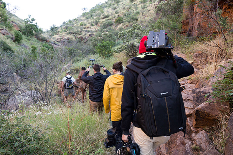 The film crew carry their equipment up the valley.